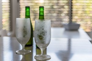 Iced glasses and green bottles