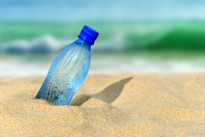 Bottle of the fresh water on sand