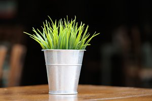 Plastic green grass in metal pot