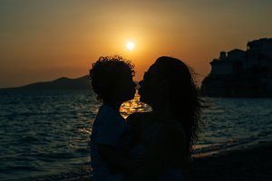 Backlit mother and son at the beach