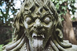 Close up view of carved traditional demon guard statue in stone in Indonesia, Bali.