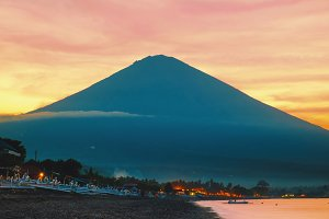Vivid orange sunset with beautiful Agung volcano view from a black sand beach and sun reflection on a sea in Bali