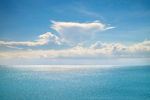 Beautiful white clouds and sun beams on a blue sky over calm sea with sunlight reflection in Bali, Indonesia.