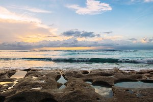 Soft sunset at a fantastic sea beach made of rocks with a holes filled by seawater in Bali