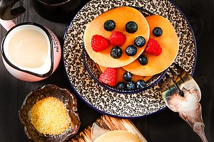 Home-made breakfast pancakes served with berries and honey