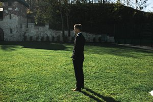 groom standing on the grass