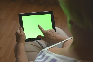 Elderly woman sitting on sofa at home and using a digital tablet pc with green screen, back view. Tablet PC in a adult woman hands