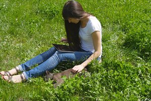 Young caucasian brunette girl sitting on grass on the meadow in the park, stroking a cat and using digital tablet pc.