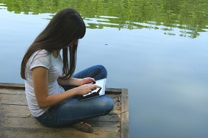 Girl using tablet pc and relaxes by the lake sitting on the edge of a wooden jetty near the water surface