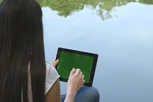 Young girl using digital tablet pc with green screen sitting on a wooden jetty by the lake. Rear view