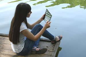 Young happy girl sitting on a wooden jetty by a lake and chatting on tablet computer
