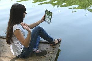 Young happy girl sitting on a jetty by a lake and chatting on tablet computer