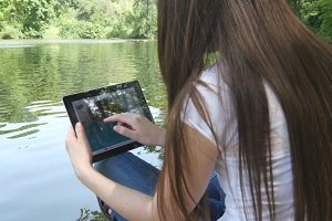 Young girl using digital tablet pc sitting on a wooden jetty by the lake. Rear view.