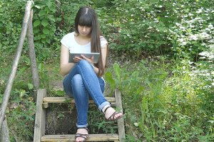 Beautiful young woman sitting on the wooden stairs in the forest and using tablet pc. Happy girl browsing Internet, using app and communicating outdoors. Relax and technology.