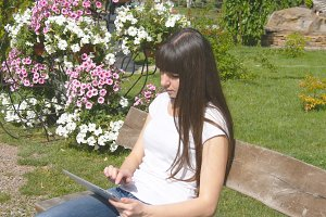 Cute young woman with tablet pc sitting on bench in the city park. Girl typing on digital tablet computer and sitting on bench in city park.
