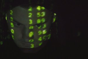 Source code projected over an angry hostile man's face, black background.