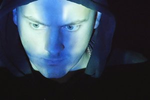 Hooded hacker working on a computer, binary code projecting on his face. Source code projected over an angry hostile man's face, black background