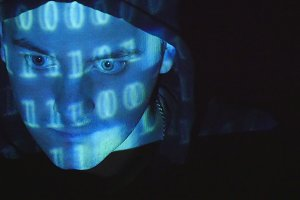 Close up shot of male face of hacker with binary code projections. Source code projected over an angry hostile man's face, black background.