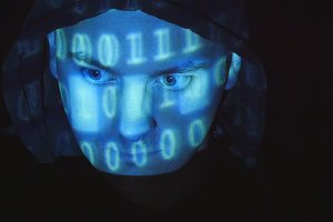 Hooded hacker working on a computer, binary code projecting on his face. Source code projected over an angry hostile man's face, black background.