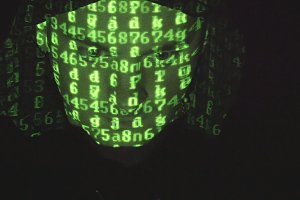 Face of male hacker in hood working on a computer while green code characters reflect on his face in a dark office room. Source code projected over an angry hostile man's face, black background.