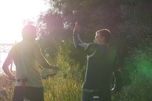 Two male friends giving high five each other and start riding bikes through forest path in sunset. Friends cycling outdoor in summer.