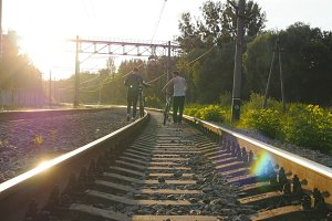 Two male friends walking with their bikes on the rails at the railway in sunset and talking. Dangerous and risky journey. Rear back view