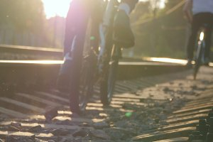Two male friends riding bicycles on the rail track in sunset. Dangerous and risky journey. Rear back view