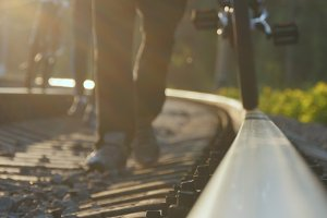Two male friends walking with their bikes on the rails at the railway towards the camera. Dangerous and risky journey.