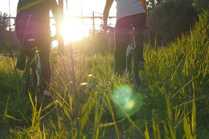 Two male bikers start riding bikes through green grass on the meadow in sunset. Friends cycling through a field in