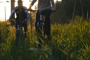 Two male bikers riding bikes through green grass on the meadow in sunset. Friends cycling through a field in summer. Low Angle View