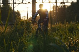 Young man riding bike through green grass on the meadow in sunset. Guy cycling through a field in summer. Low Angle View