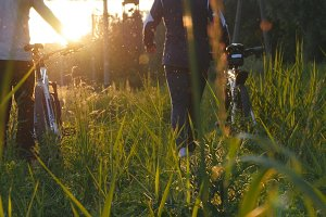 Two male friends walking with their bikes through green grass on the meadow in sunset and talking. Rear back view