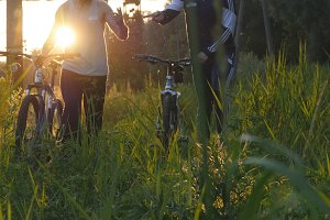 Two male friends walking with their bikes through green grass on the meadow in sunset and talking.