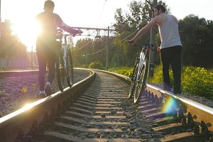 Two male friends walking with their bikes on the rails at the railway in sunset and talking.