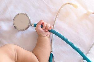 stethoscope in hand of newborn baby