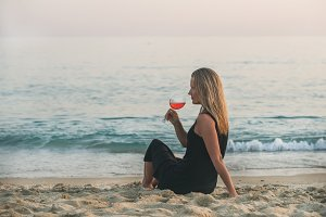 Woman with glass wine near the sea