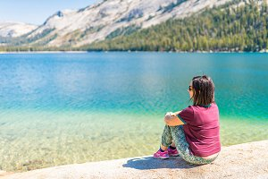 Woman sitting on alpine mountain lake, Yosemite National Park
