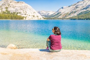 Woman sitting on alpine mountain lake, Yosemite National Park
