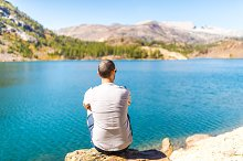 Man sitting on alpine mountain lake