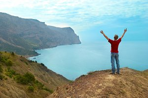 Happy man standing on the cliff