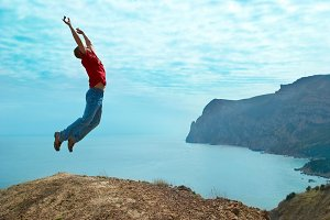 Man jumping cliff against sea