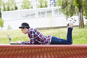 young man with laptop outdoors