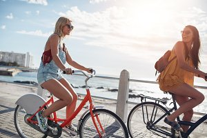 Best friends cycling along seaside