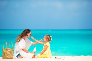 Little adorable girl applying sun cream to her mother nose