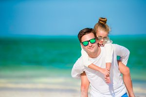 Happy father and kid together on white tropical beach