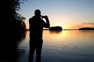 Young man photographing sunset