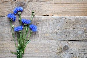 Cornflowers on wooden background