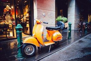 Orange Scooter Bike parks on street