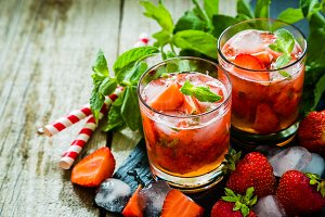 Strawberry mojito and ingredients on rustic background
