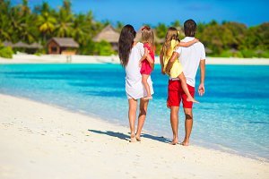 Happy beautiful family vacation on white beach